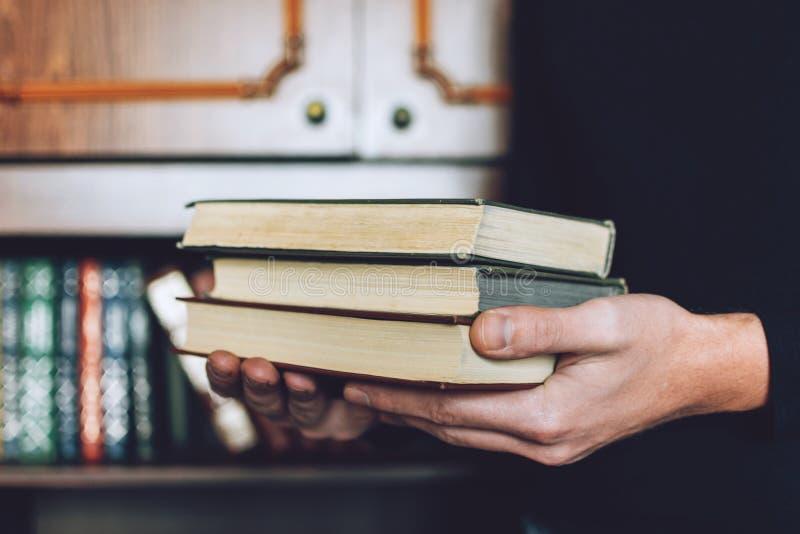 Mens, Student die vele boeken in handen op de achtergrond van boekenrekken houden De mannelijke handen houden een grote stapel bo royalty-vrije stock afbeelding