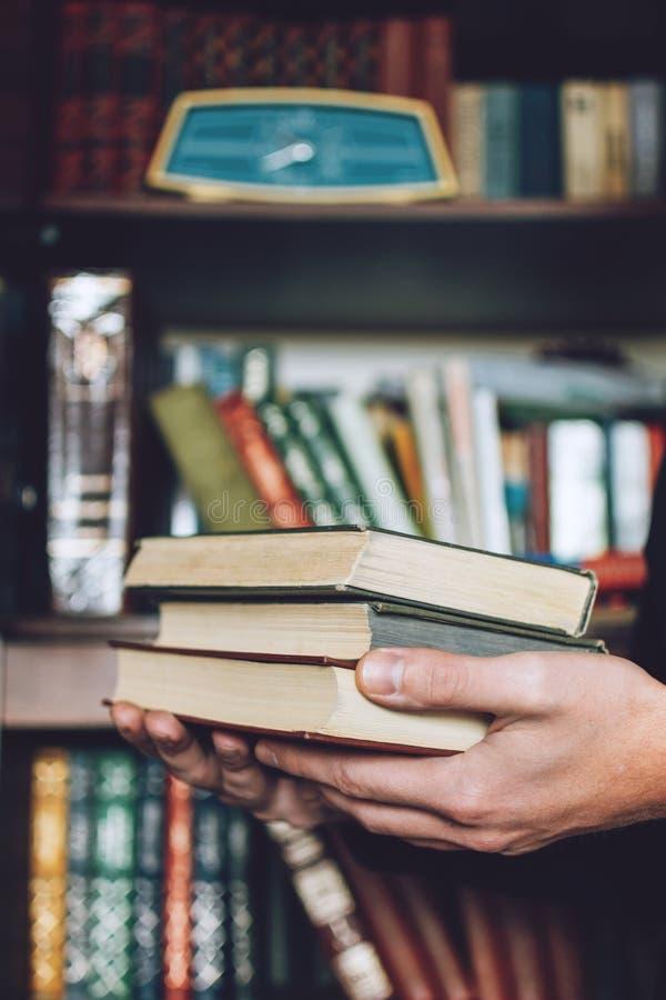 Mens, Student die vele boeken in handen op de achtergrond van boekenrekken houden De mannelijke handen houden een grote stapel bo stock afbeeldingen