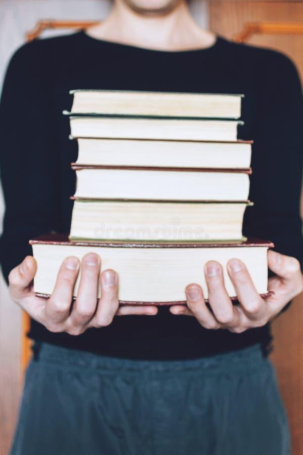 Mens, Student die vele boeken in handen op de achtergrond van boekenrekken houden De mannelijke handen houden een grote stapel bo stock fotografie