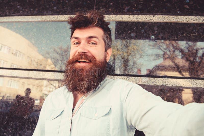 Mens, toerist met baard en snor op vrolijk, het glimlachen gezicht, zwarte marmeren achtergrond Het concept van de Selfiefoto hip royalty-vrije stock afbeelding
