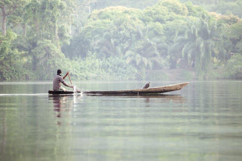 Mens in Traditionele Boot op Tropische Rivier Volta in Ghana, het Westen A stock afbeelding