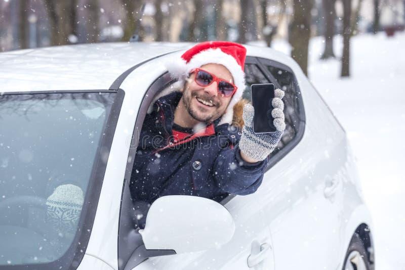 Mens uit autoraam die Santa Claus-hoed dragen en lege het scherm slimme telefoon houden stock afbeelding