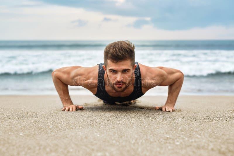 Mens Uitoefenen, die Duw op Oefeningen op Strand doen Geschiktheidstraining royalty-vrije stock foto