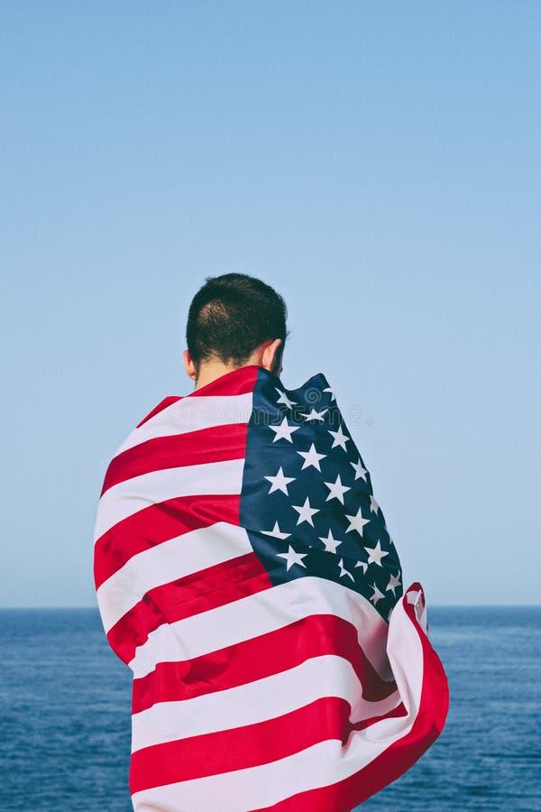 Mens van achter verpakt in Amerikaanse Vlag tegen blauwe hemel royalty-vrije stock fotografie