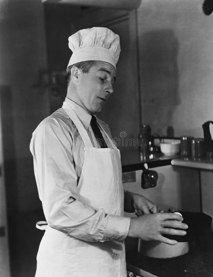 Mens in van de chef-kokhoed en schort het koken royalty-vrije stock foto's