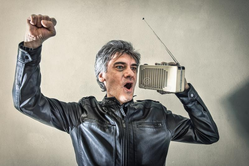 Mens verheugen die aan radio luisteren stock foto's