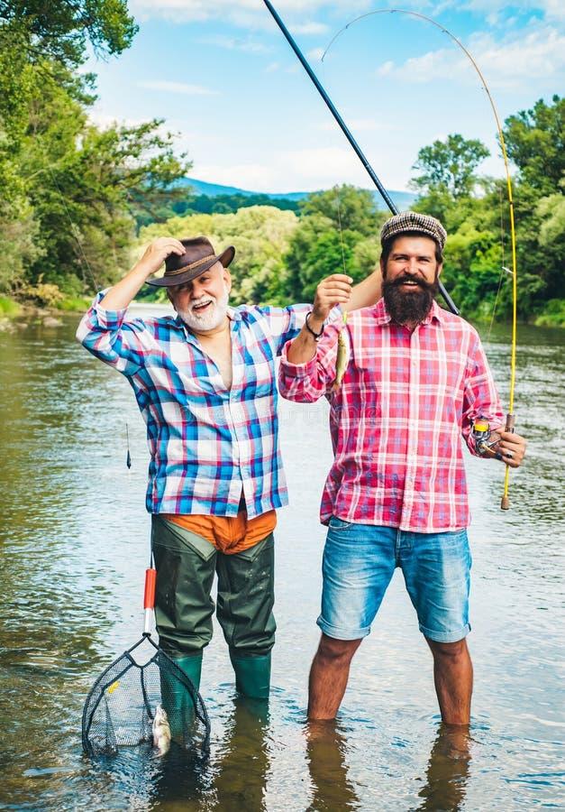 Mens visserij Mensen die in rivier tijdens de zomerdag vissen Vader en Zoons Visserij Vliegstaaf en spoel met een bruine forel va royalty-vrije stock foto