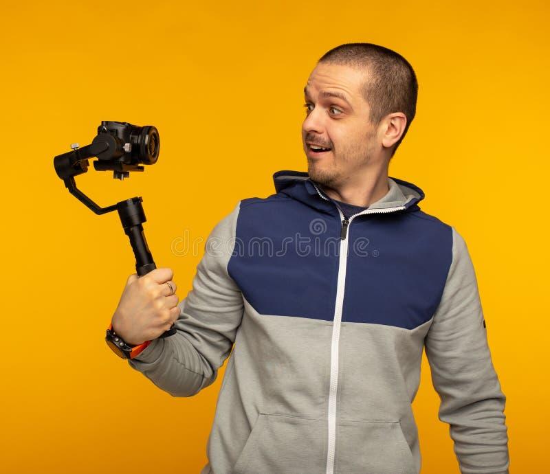 Mens vlogger of videographer film zelf gebruikende camera op gimbal royalty-vrije stock foto's