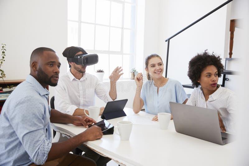 Mens in VR-beschermende brillen bij een bureau met collega's in een bureau stock afbeelding