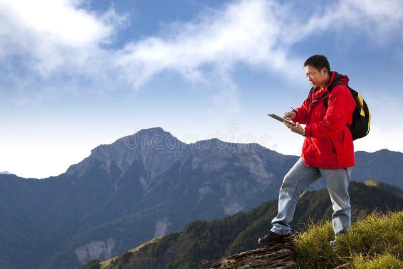 Mens wat betreft tabletPC op de berg royalty-vrije stock fotografie