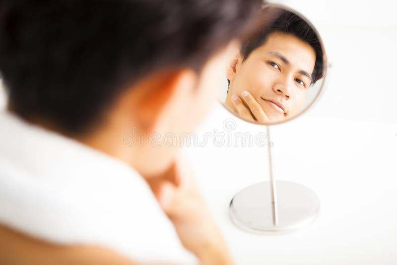 mens wat betreft zijn vlot gezicht na het scheren stock afbeelding