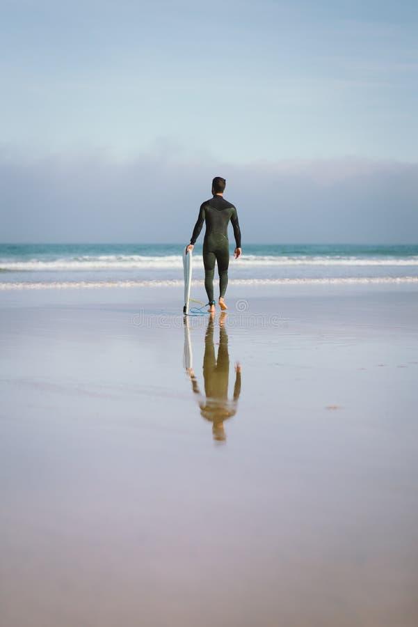 Mens in wetsuit die naar het overzees voor het surfen gaan royalty-vrije stock foto