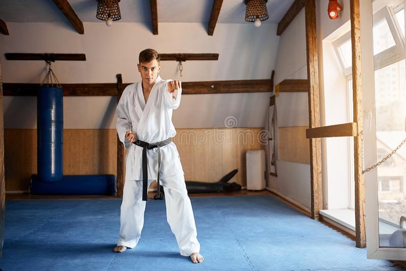 Mens in witte kimono met zwart band opleidingskarate in gymnastiek stock foto's
