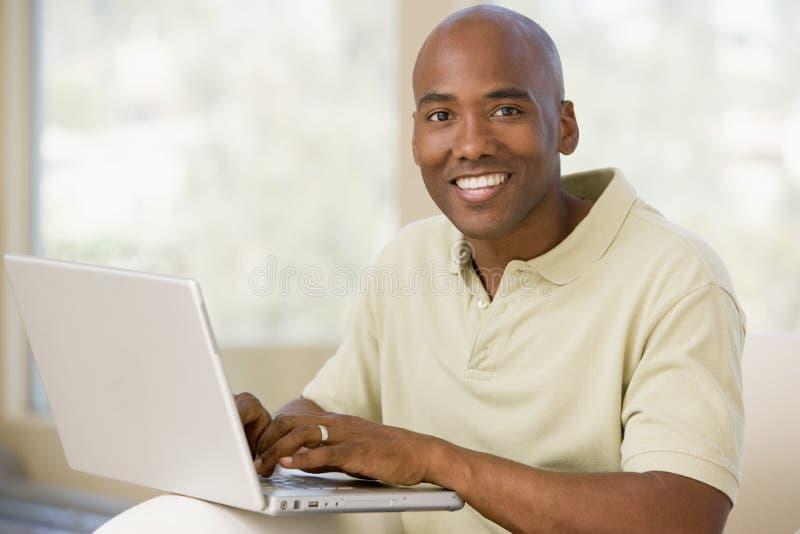 Mens in woonkamer die laptop en het glimlachen gebruikt royalty-vrije stock afbeelding