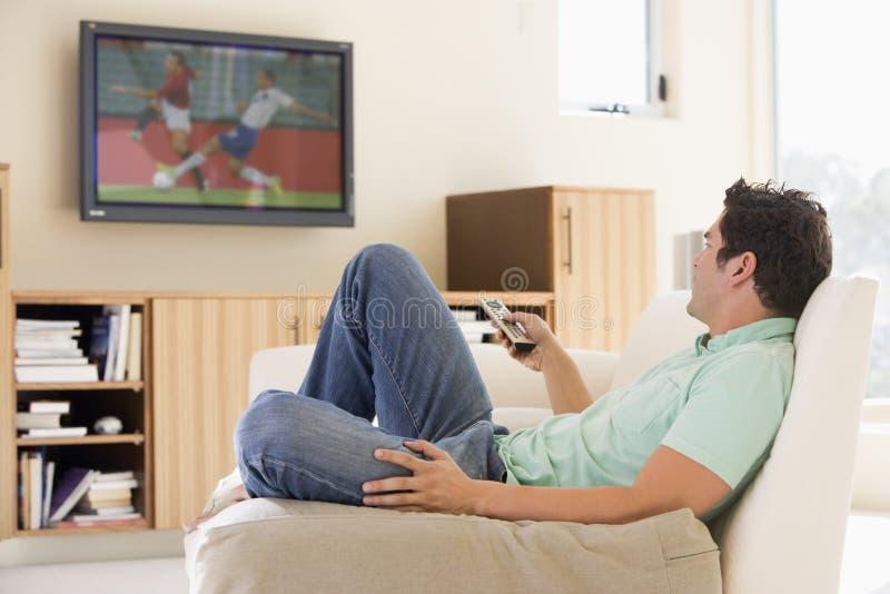 Mens in woonkamer het letten op televisie stock foto