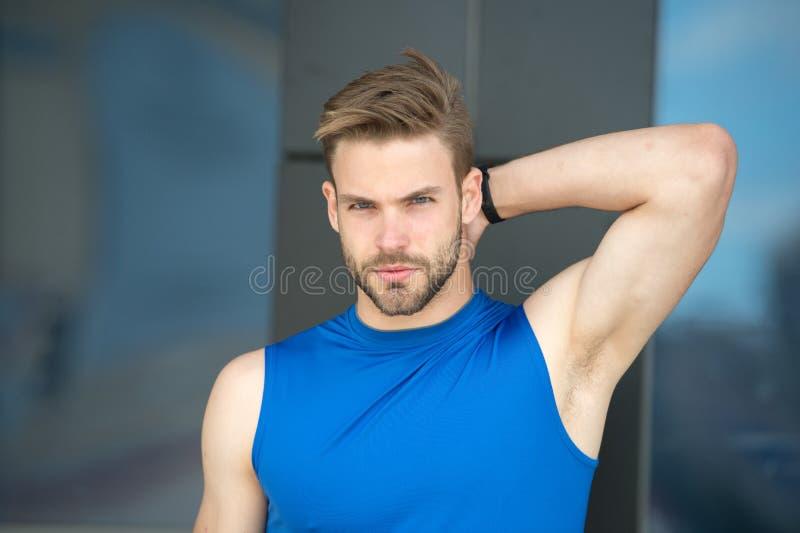 Mens zeker in zijn transpiratiewerend middel Sportman na opleiding tevreden met transpiratiewerend middel De kerel controleert dr stock foto