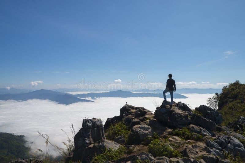 Mens zich op de klip bevinden en de vallei bekijken en bergen die in het daglicht stock fotografie