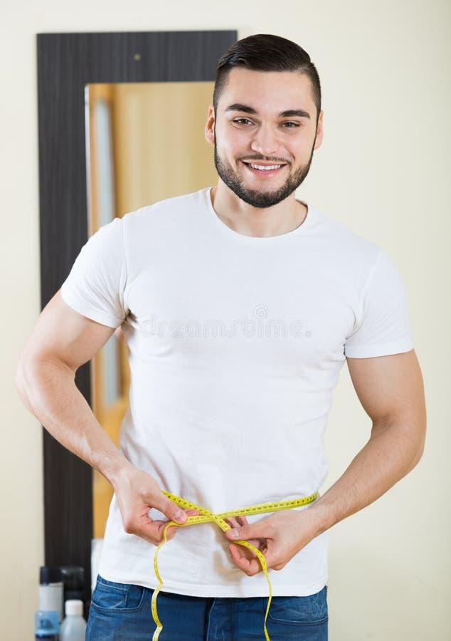 Mens zijn bicep meten en lichaam die royalty-vrije stock foto