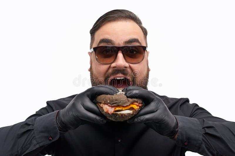 Mens in zonnebril die hamburger bijten stock afbeelding