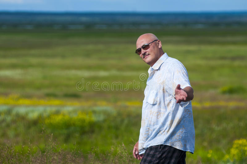 Mens in zonnebril met vriendschappelijk gezicht het uitnodigen gebaar op gebiedsachtergrond stock foto's