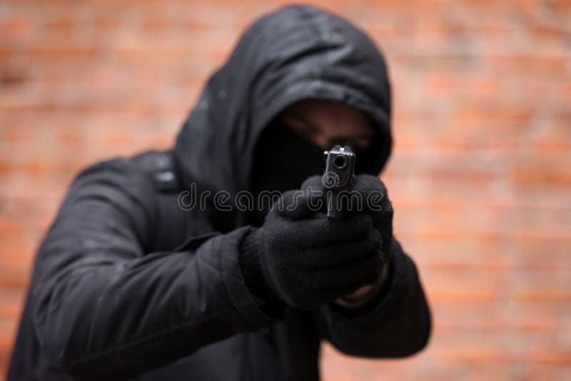Mens in zwart masker met pistool stock afbeeldingen