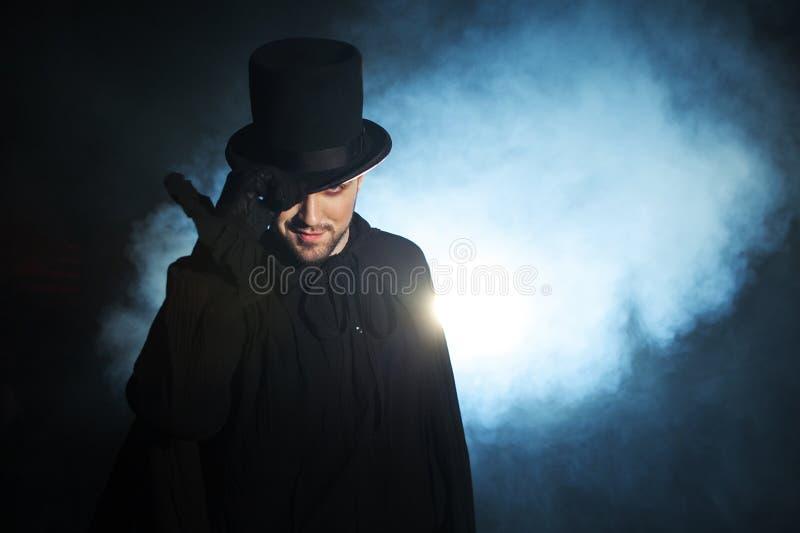 Mens in zwarte hoge zijden en een mantel Duivels beeld Tovenaarillusionist royalty-vrije stock foto's