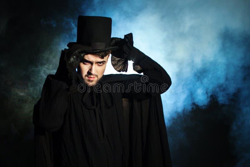 Mens in zwarte hoge zijden en een mantel Duivels beeld Tovenaarillusionist royalty-vrije stock afbeeldingen