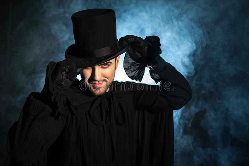 Mens in zwarte hoge zijden en een mantel Duivels beeld Tovenaarillusionist stock afbeelding
