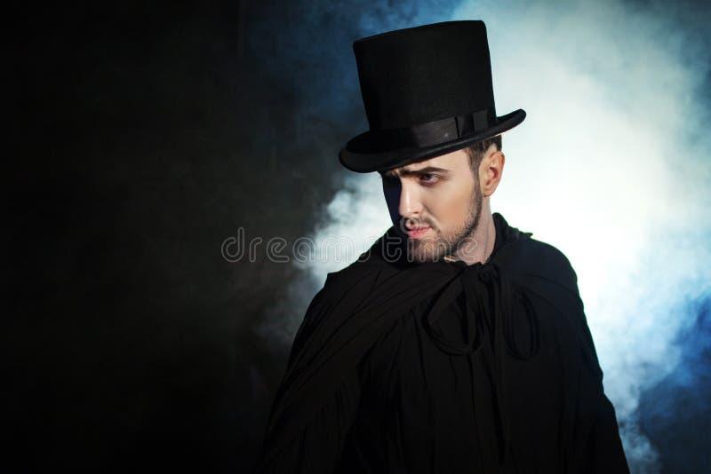 Mens in zwarte hoge zijden en een mantel Duivels beeld Tovenaarillusionist stock foto's