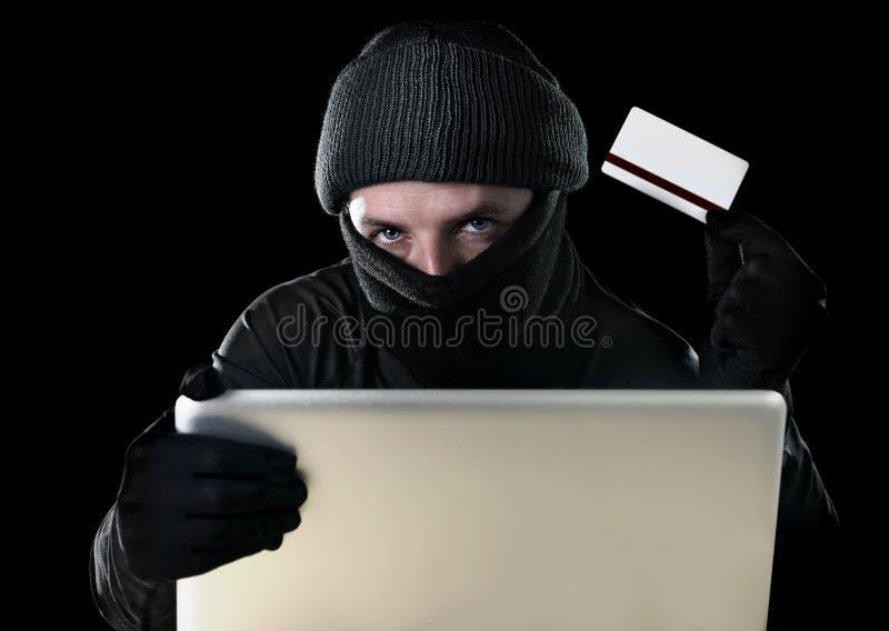 Mens in zwarte holdingscreditcard die computerlaptop voor criminele activiteit het binnendringen in een beveiligd computersysteem stock foto
