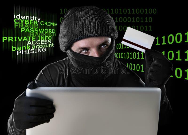 Mens in zwarte holdingscreditcard die computerlaptop voor criminele activiteit het binnendringen in een beveiligd computersysteem royalty-vrije stock foto's