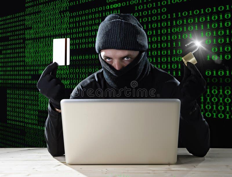 Mens in zwarte holdingscreditcard en slot die computerlaptop voor criminele activiteit het binnendringen in een beveiligd compute royalty-vrije stock fotografie