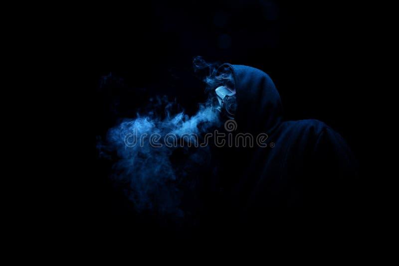 Mens in zwarte kap in de aangestoken nachtduisternis, vaag, concepten van royalty-vrije stock foto's
