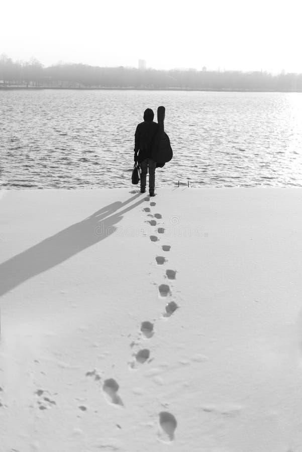 Mens in zwarte met koffer en gitaar die naar water in wintertijd lopen royalty-vrije stock afbeelding