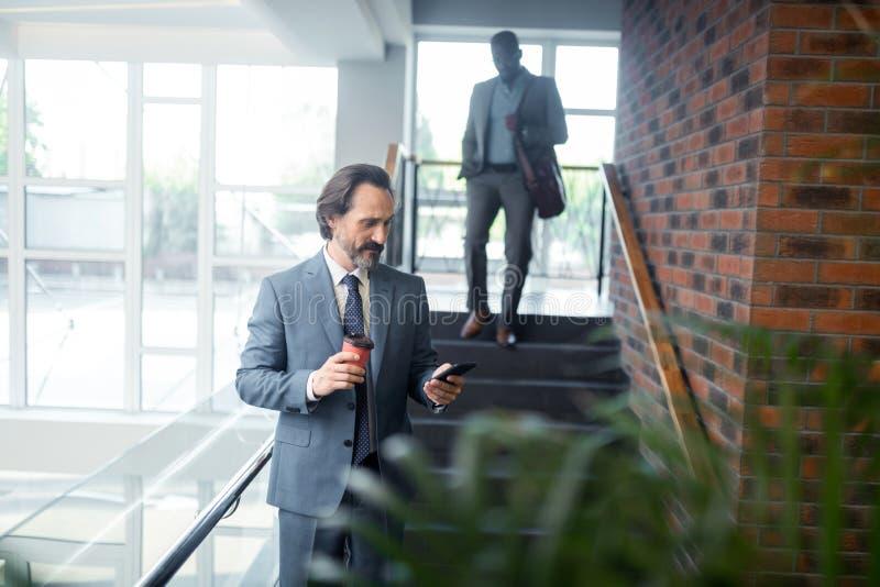 Mensagem cinzento-de cabelo farpada da leitura do trabalhador de escritório no smartphone fotos de stock