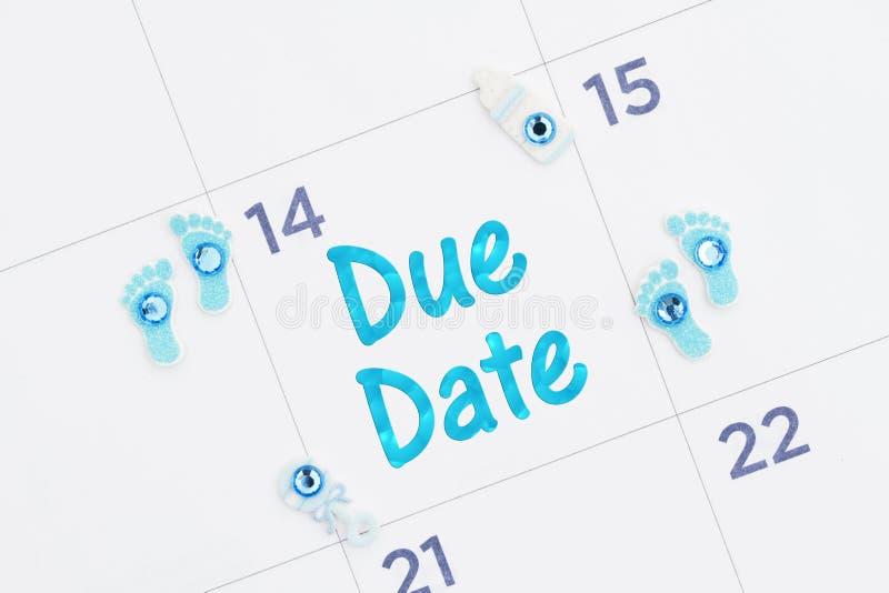 Mensagem da data aprazada em um calendário mensal com pegadas minúsculas, garrafa e chocalho do bebê imagem de stock royalty free