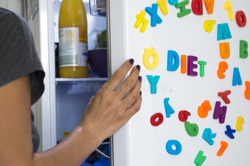 Mensagem da dieta das letras coloridas no refrigerador branco com a mulher com fome que olha para dentro fotografia de stock
