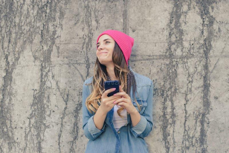 Mensagem da moça com seu melhor amigo Menina que lê e que datilografa sms engraçados em seu telefone celular, pilha, celular, tel fotos de stock royalty free