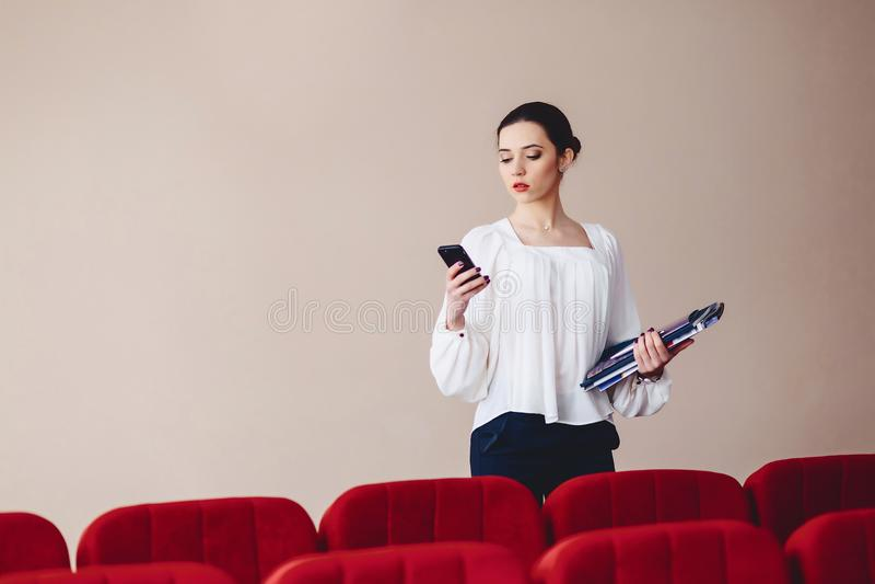 Mensagem da mulher de negócio no telefone com originais em suas mãos imagem de stock royalty free