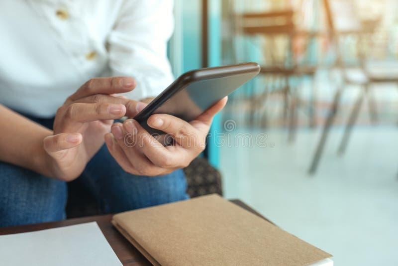 Mensagem das mãos de uma mulher que guardam, da utilização e texting do telefone esperto no café imagens de stock