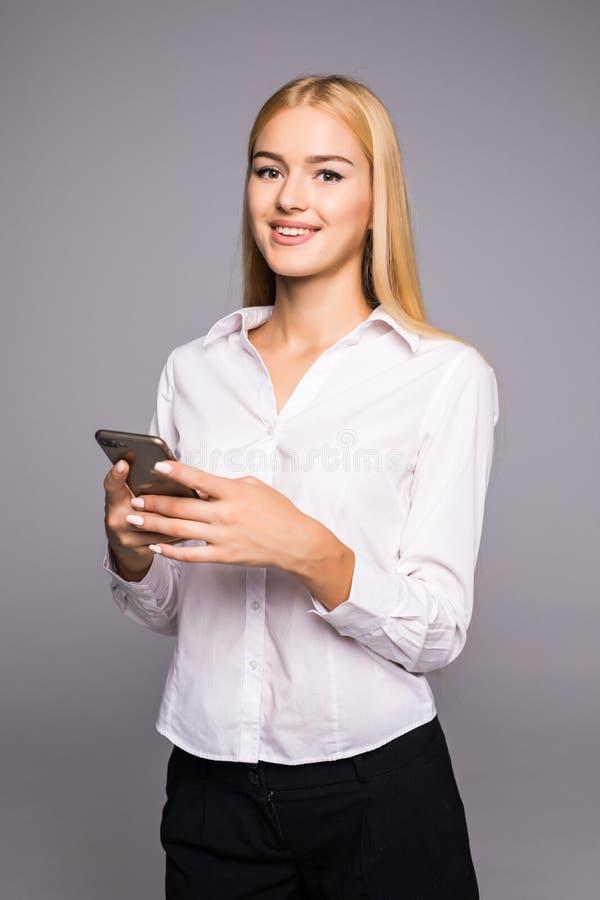 Mensagem de datilografia da jovem mulher no smartphone menina de sorriso bonita que usa seu telefone celular, fundo cinzento do e foto de stock
