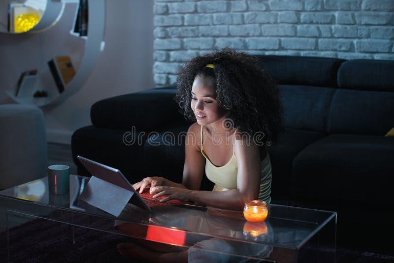 Mensagem de datilografia da mulher nova de Latina no portátil na noite fotos de stock royalty free