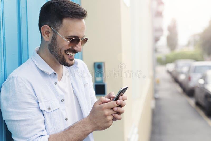 Mensagem de datilografia do homem na frente da porta azul fotos de stock royalty free