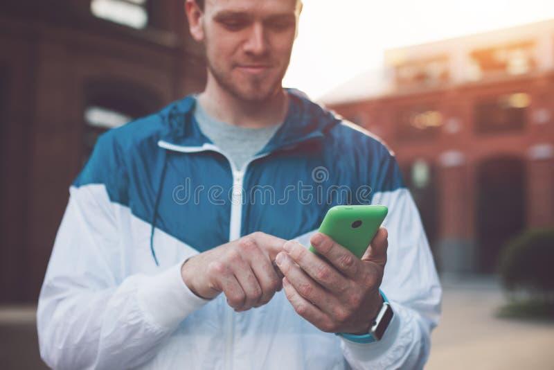 Mensagem de datilografia em seu telefone celular, por do sol do homem novo na rua foto de stock royalty free