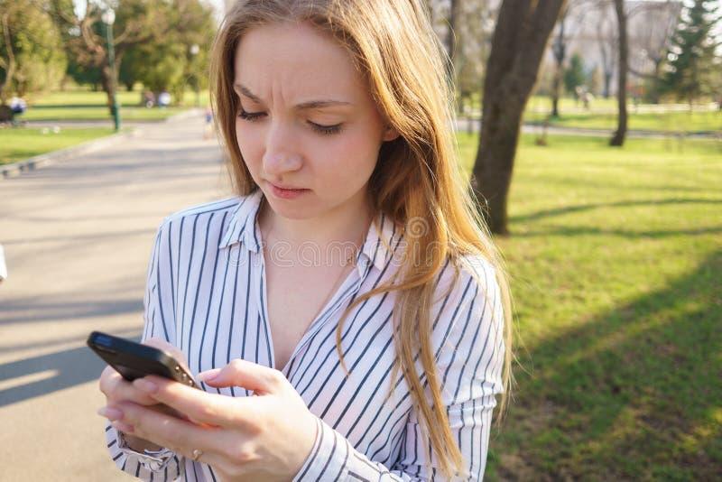 Mensagem de datilografia preocupada nova da mulher em seu telefone esperto Povos, r imagens de stock