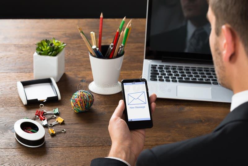 Mensagem de Looking At New do homem de negócios no telefone celular imagem de stock