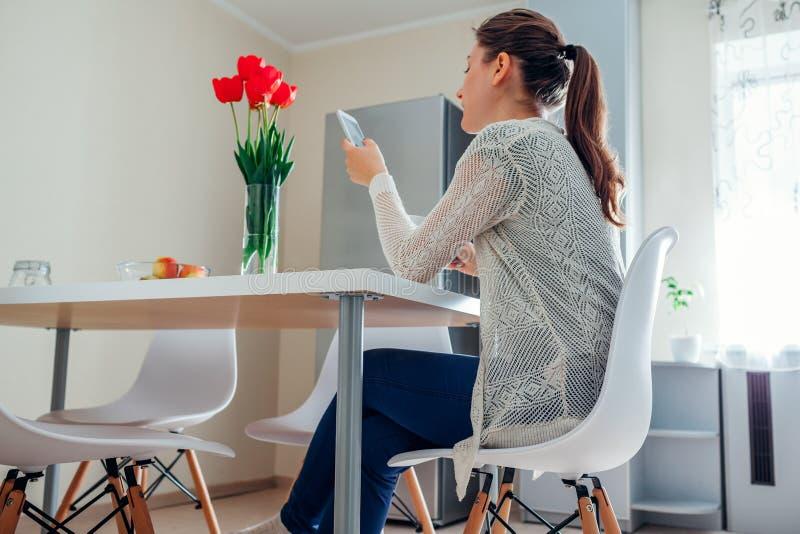 Mensagem de relaxamento e de datilografia da jovem mulher no telefone na cozinha Chá bebendo da menina Projeto moderno da cozinha fotos de stock
