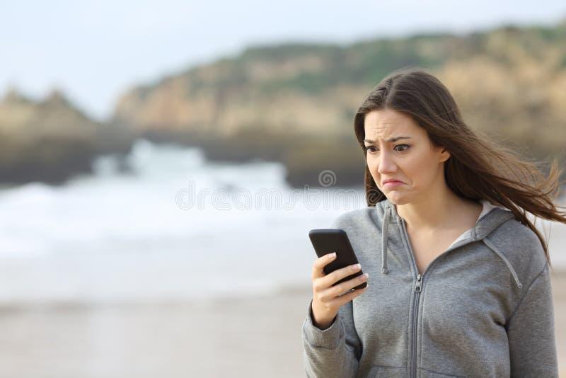Mensagem de telefone adolescente desapontado da leitura na praia imagem de stock