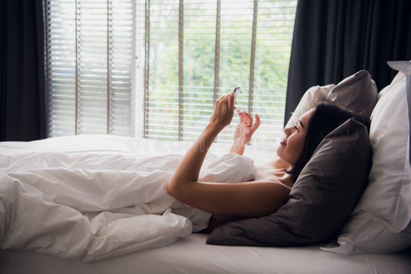 Mensagem de texto bonita da leitura da jovem mulher em no seu telefone celular e sorriso imagens de stock