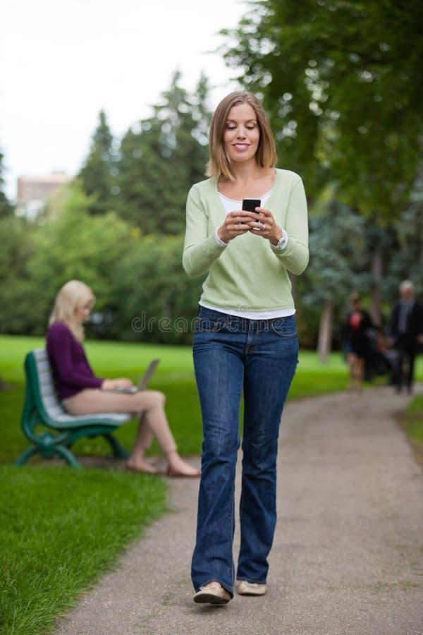 Mensagem de texto da leitura da mulher no parque fotografia de stock